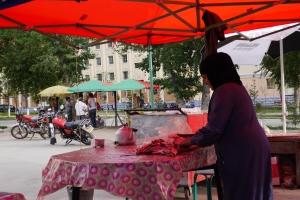 Traditional Muslim woman makes BBQ in Keketuohi Town