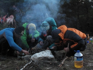 Group effort to make fire in the wet